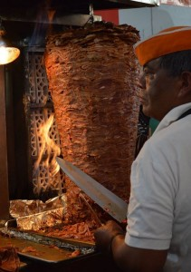 Al pastor meat cooking on spit in front of fire. Man with knife ready to carve meat